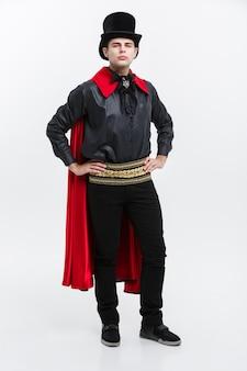 Vampire halloween concept - retrato de corpo inteiro de vampiro caucasiano bonito em traje de halloween preto e vermelho.