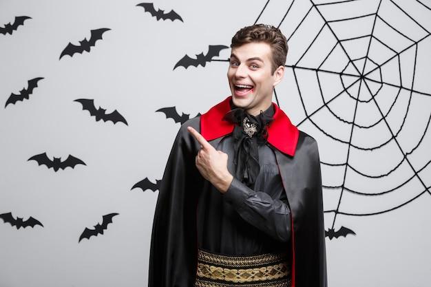 Vampire halloween concept - retrato de um belo caucasiano em vampiro traje de halloween, apontando para o lado.