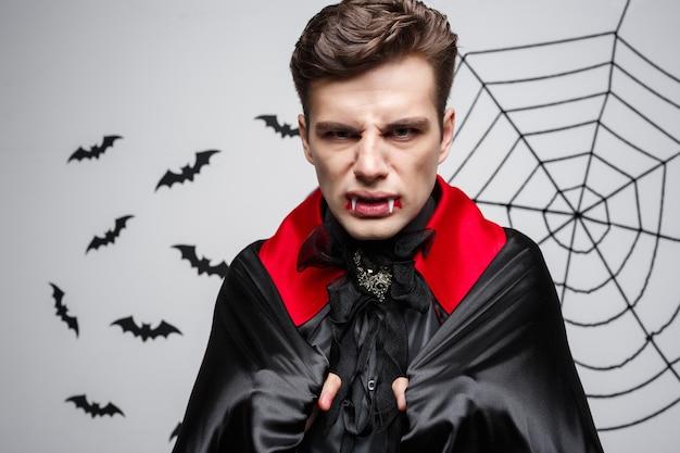 Vampire halloween concept - retrato de um vampiro caucasiano com raiva gritando.