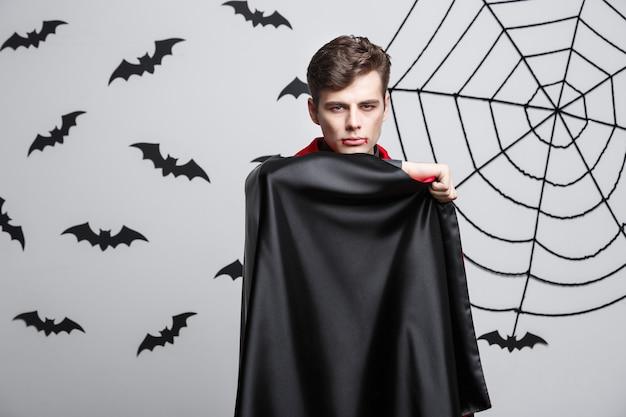Vampire halloween concept - retrato de uma bela fantasia de vampiro caucasiano esvoaçando sua capa vermelha e preta.