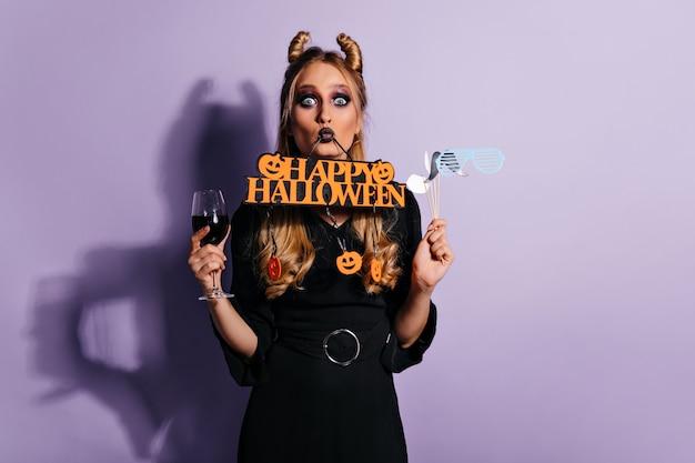 Vampiro jovem brilhante posando no halloween. bruxa loira espantada em roupa preta bebendo sangue.