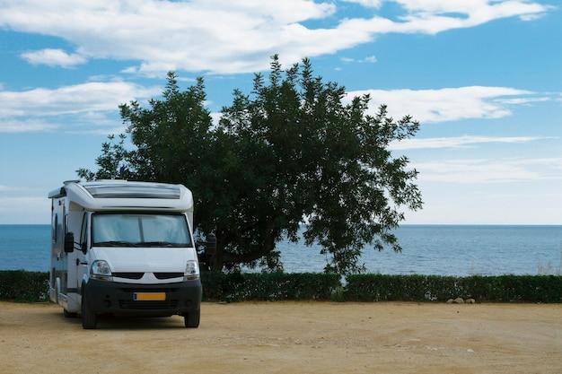 Van com trailer de viagem estacionado em um lindo acampamento com vista para o litoral