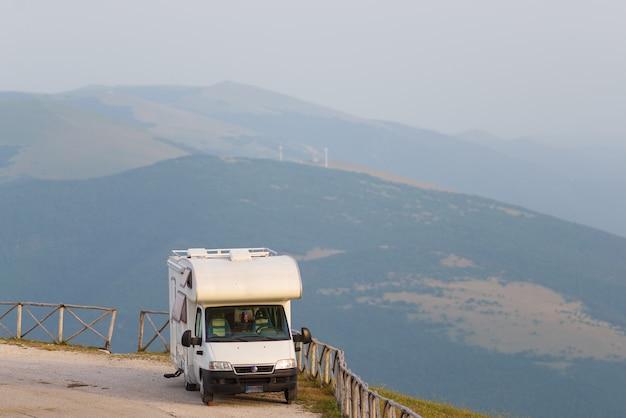 Van de campista na beira da estrada numa bela paisagem. céu dramático ao pôr do sol, nuvens cênicas acima das montanhas e montanhas únicas na itália, conceito alternativo de férias vanlife.