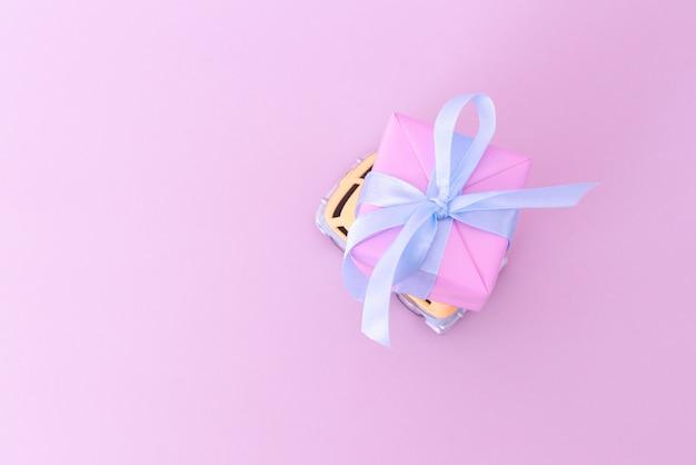 Van de hippie de carro de brinquedo retrô entregando presente em rosa
