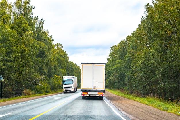 Vans de carga viajam ao longo de uma estrada florestal em um dia de verão, transporte de carga de longa distância