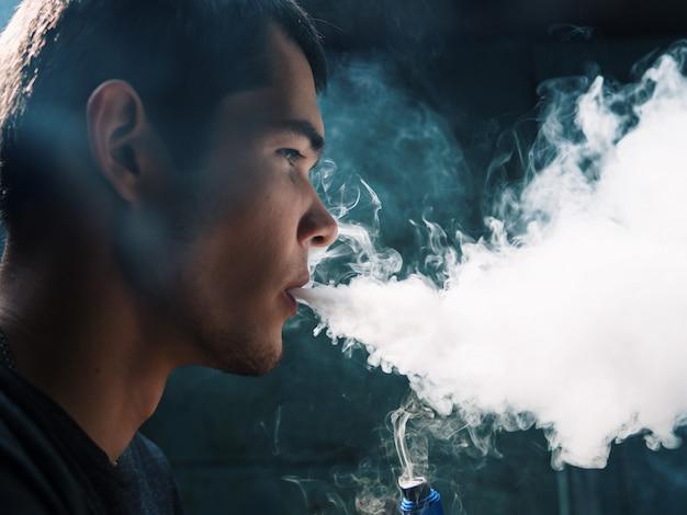 Vaper masculino em uma nuvem escura do close up do fundo do vapor