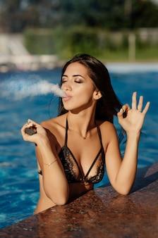 Vaping conceito. mulher morena sexy lingerie preta vaping na piscina e mostra um sinal de mão ok. uma nuvem de vapor. mulher sexy com corpo legal vaping e libera uma nuvem de vapor. vista de perto.