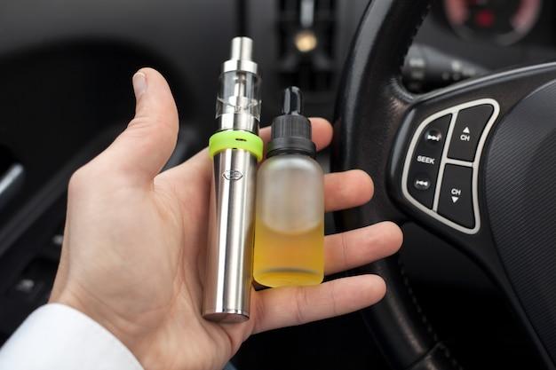 Vaping dispositivo e e-líquido na mão do homem.