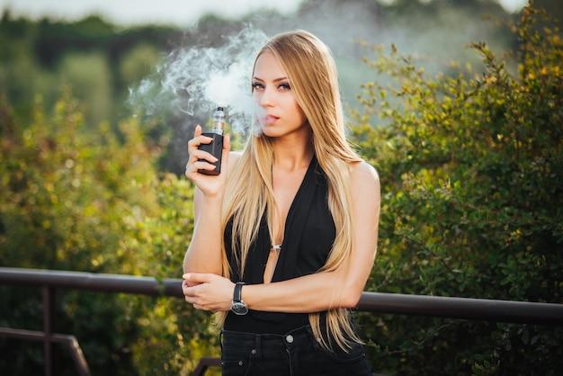 Vaping e-cigarro de fumo da mulher bonita nova com fumo ao ar livre.