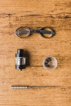 Vaping ferramentas com fundo de madeira, scisors, atomizador, vertical da bobina