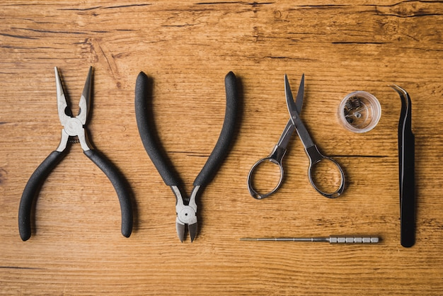 Vaping ferramentas com fundo de madeira, scisors, atomizador