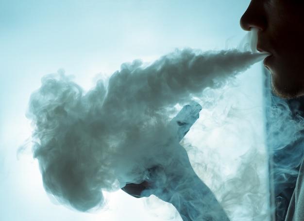 Vaping um cigarro eletrônico com muita fumaça.