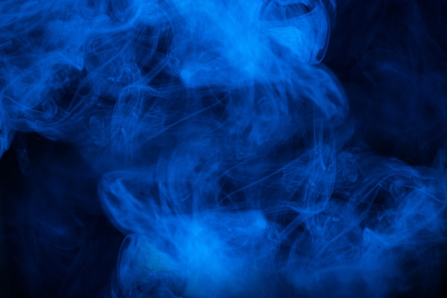 Vapor azul sobre um fundo preto. copie o espaço.
