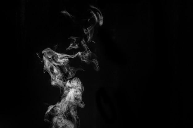 Vapor branco encaracolado místico perfeito ou fumaça isolada na superfície preta.