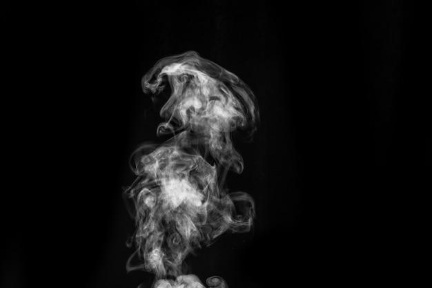 Vapor branco encaracolado místico perfeito ou fumaça isolada no fundo preto. névoa ou poluição atmosférica de fundo abstrato, elemento de design para o halloween, layout para colagens.