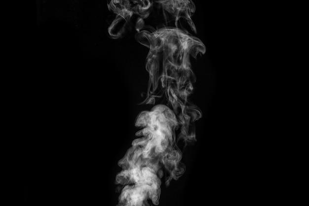 Vapor branco encaracolado místico perfeito ou fumaça isolada no fundo preto. nevoeiro abstrato ou poluição atmosférica, elemento de design para o halloween, layout para colagens.