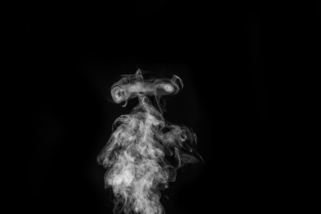 Vapor branco encaracolado ou fumaça isolada na superfície preta.