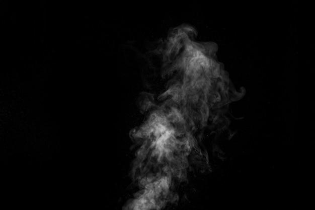 Vapor branco encaracolado subindo isolado em um fundo preto