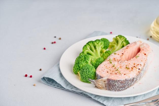 Vapor de salmão e brócolis, paleo, keto ou dieta fodmap. chapa branca na mesa azul, vista lateral