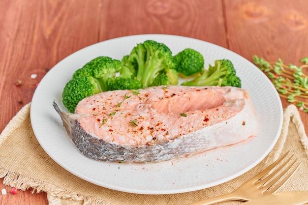 Vapor de salmão e legumes, paleo, keto, dieta fodmap. chapa branca na mesa rústica