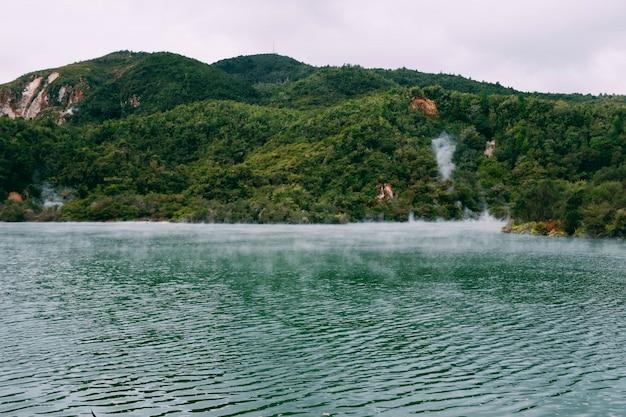 Vapor saindo de um belo corpo de água cercado por montanhas verdes