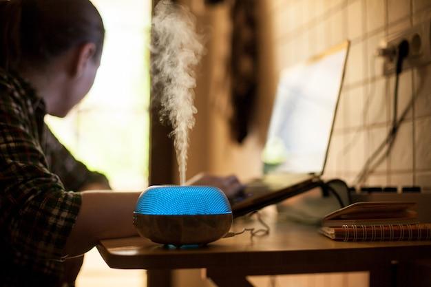 Vapor saindo do diffureser de óleo essencial com led azul enquanto mulher trabalhava no laptop.