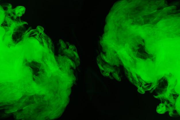 Vapor verde sobre um fundo preto. copie o espaço.
