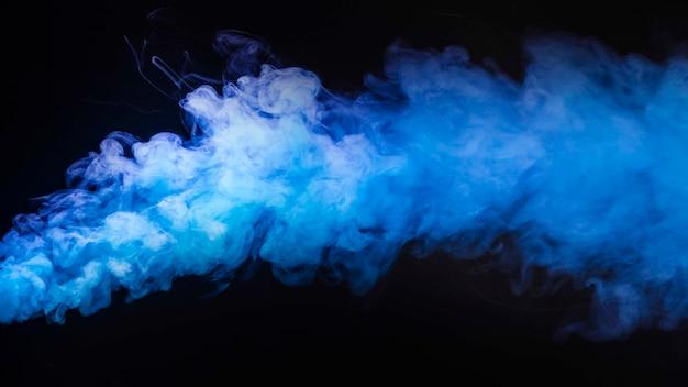 Vapores densos de fumaça azul abstrata em fundo escuro