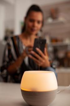 Vaporizador com óleos essenciais na cozinha e mulher relaxando