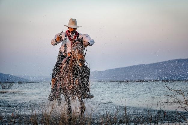 Vaqueiro cavalgando um cavalo, cruzando o rio