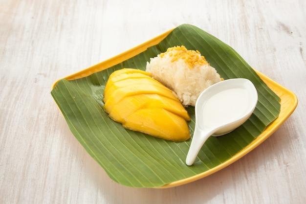 Vara de arroz com manga na folha de bananeira e placa amarela sobremesa tailândia