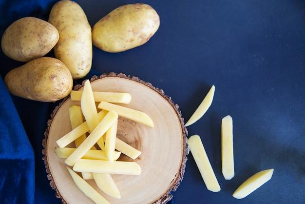 Vara de batata cortada pronta para fazer batatas fritas - conceito de preparação de comida tradicional