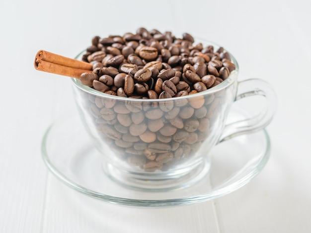Vara de canela em grãos de café torrados em uma tigela de vidro em uma mesa de madeira branca.
