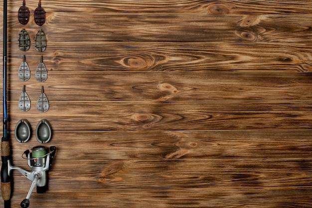 Vara de pesca com acessórios em mesa de madeira
