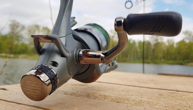 Vara de pesca de carpa isolada no lago e ponte de madeira