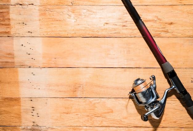 Vara de pesca e carretel de pesca em pano de fundo de madeira