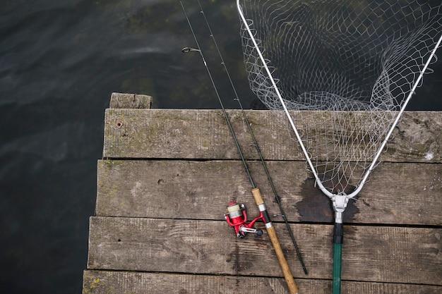 Vara de pesca e rede de pesca na beira do cais de madeira sobre o lago