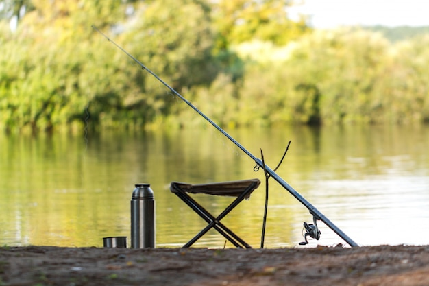 Vara de pesca, garrafa térmica, cadeira de pesca no fundo do lago. pescaria.