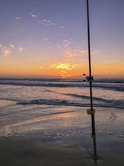 Vara de pesca na praia ao pôr do sol, elenco de surfe