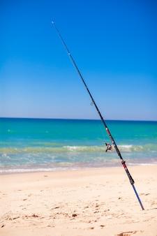 Vara de pescar na areia branca na praia tropical