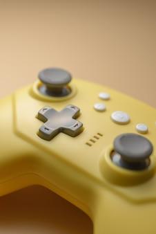Vara de um close-up de controlador de jogo amarelo. videogames, entretenimento em casa. close-up de botões amarelos no joystick sem fio. conceito de jogo móvel.