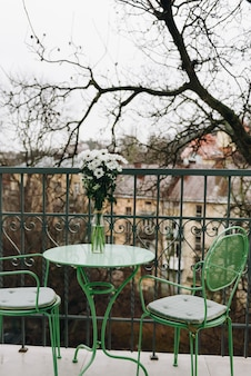 Varanda aconchegante com mesa e cadeiras verdes