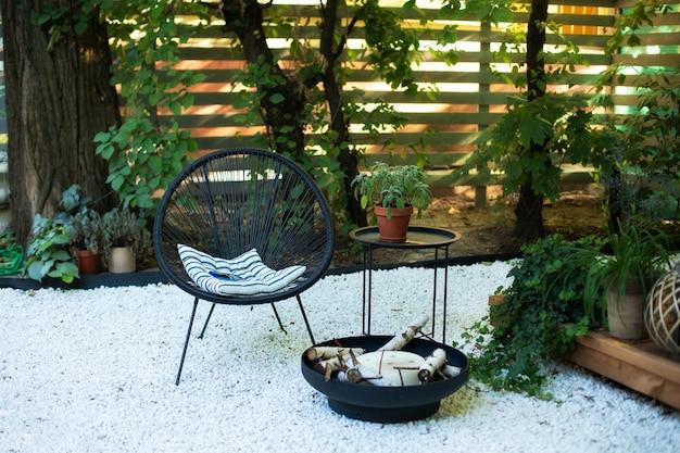 Varanda casa com poltronas, mesa e vasos de plantas, tigela de lareira no jardim no quintal dos fundos