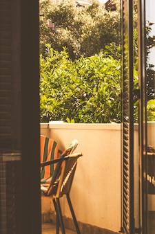 Varanda com cadeiras contra o fundo do jardim, vista de dentro