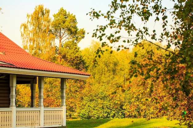 Varanda com telhado vermelho no contexto de uma floresta de outono em um dia ensolarado de habitação na natureza i ...