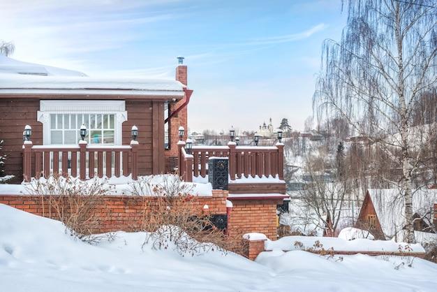 Varanda de madeira do museu na neve e vista do templo ao longe em plyos à luz de um dia de inverno sob um céu azul