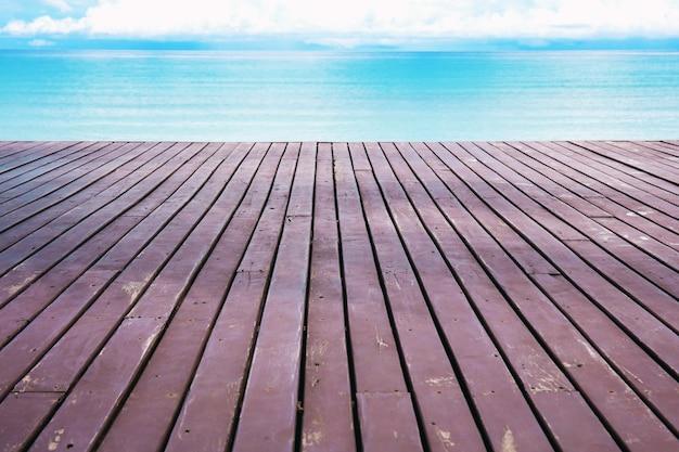 Varanda de madeira que se estende até o mar no céu.