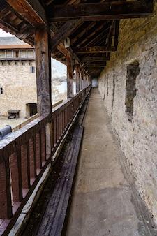 Varanda velha medieval com corrimão e teto de madeira em perspectiva longa.