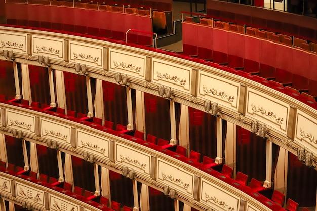 Varandas vermelhas agradáveis do teatro de viena muito decoradas e sem pessoas.
