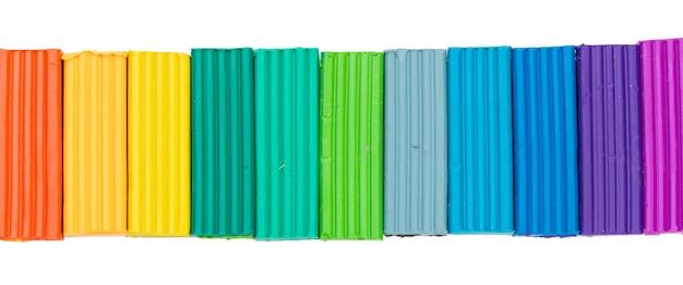 Varas coloridas da massa de modelar isoladas sobre o branco